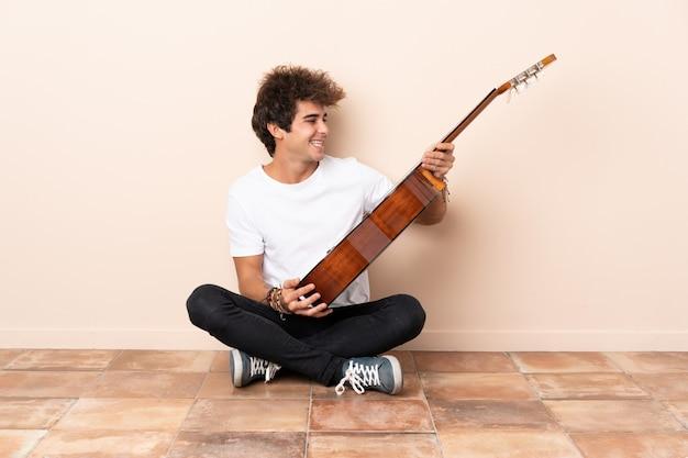 Jonge blanke man met een gitaar zittend op de vloer met gelukkige uitdrukking