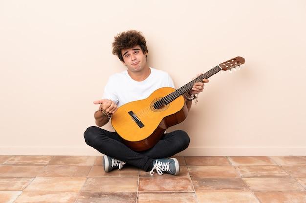 Jonge blanke man met een gitaar zittend op de vloer twijfels gebaar maken terwijl het opheffen van de schouders