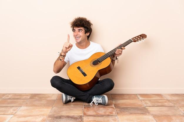 Jonge blanke man met een gitaar zittend op de vloer van plan om de oplossing te realiseren terwijl hij een vinger opheft
