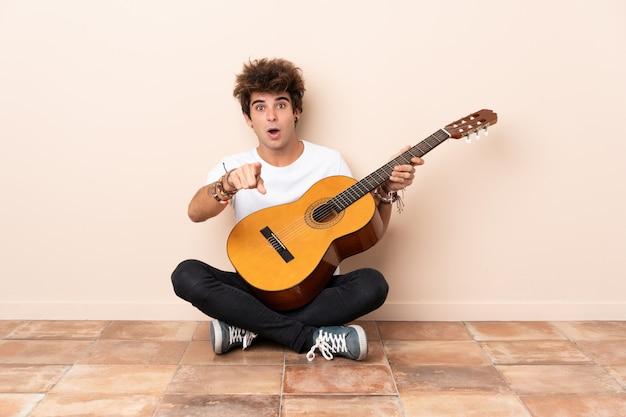 Jonge blanke man met een gitaar zittend op de vloer verrast en voorzijde wijzen