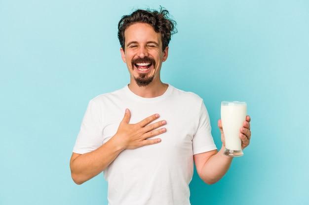 Jonge blanke man met een glas melk geïsoleerd op blauwe achtergrond lacht hardop terwijl hij de hand op de borst houdt.