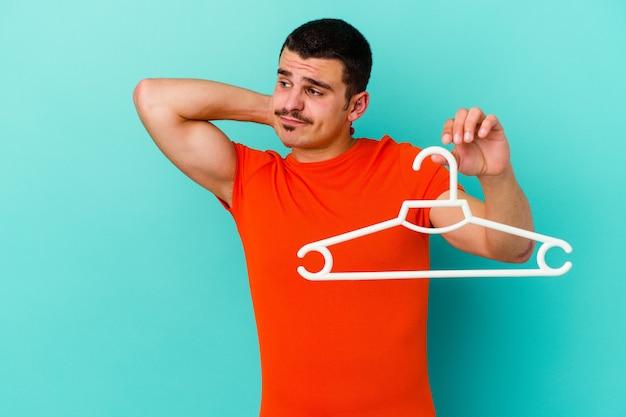 Jonge blanke man met een hanger geïsoleerd op blauwe muur achterkant van het hoofd aanraken, denken en een keuze maken