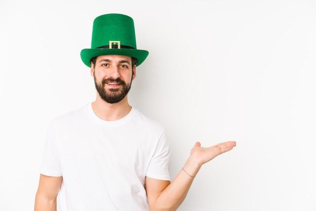 Jonge blanke man met een heilige patricks hoed geïsoleerd met een kopie ruimte op een palm en met een andere hand op de taille.