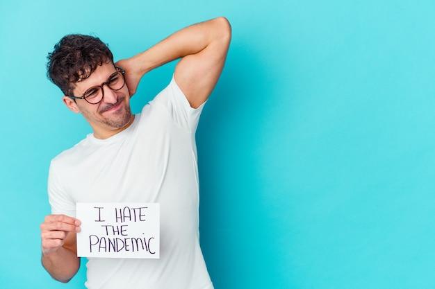 Jonge blanke man met een i hate the pandemic plakkaat geïsoleerd achterhoofd aanraken, nadenken en een keuze maken