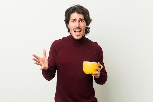 Jonge blanke man met een koffiekopje een overwinning of een succes vieren