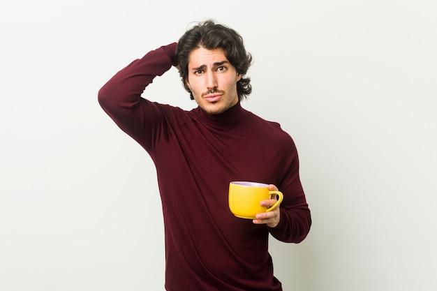 Jonge blanke man met een kopje koffie wordt geschokt, ze heeft belangrijke vergadering onthouden.