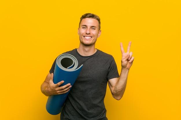 Jonge blanke man met een mat met nummer twee met vingers.