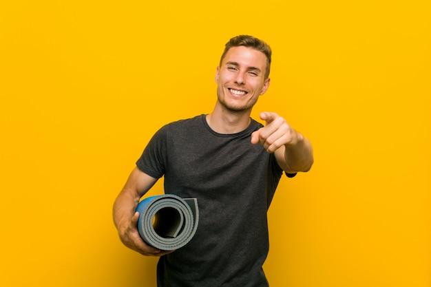Jonge blanke man met een mat vrolijke glimlach wijzend naar de voorkant.
