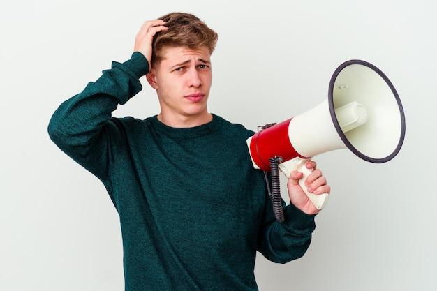 Jonge blanke man met een megafoon geïsoleerd op een witte muur wordt geschokt, ze herinnert zich een belangrijke bijeenkomst.