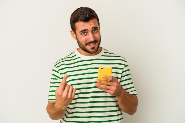 Jonge blanke man met een mobiele telefoon geïsoleerd op een witte muur wijzend met de vinger naar je alsof uitnodigend dichterbij komen