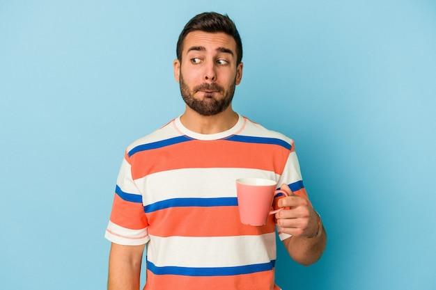 Jonge blanke man met een mok geïsoleerd op blauwe muur verward, twijfelachtig en onzeker.