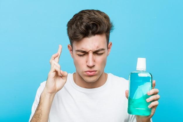 Jonge blanke man met een mondwater kruising vingers voor het hebben van geluk