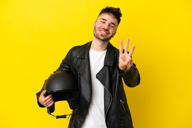 Jonge blanke man met een motorhelm geïsoleerd op gele achtergrond gelukkig en drie tellen met vingers
