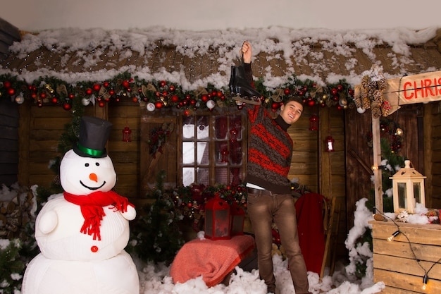 Jonge blanke man met een paar schaatsen op een versierd houten huis met wintersneeuwpop en kerstcabinedecors.