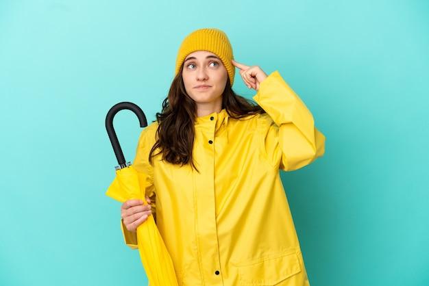 Jonge blanke man met een paraplu geïsoleerd op een blauwe achtergrond met twijfels en denken