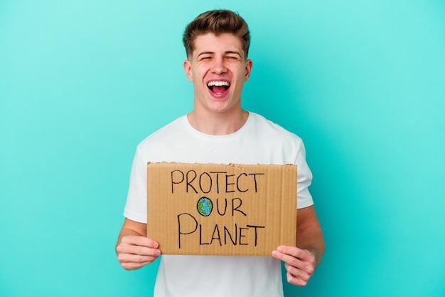 Jonge blanke man met een plakkaat van onze planeet te beschermen geïsoleerd op blauwe muur