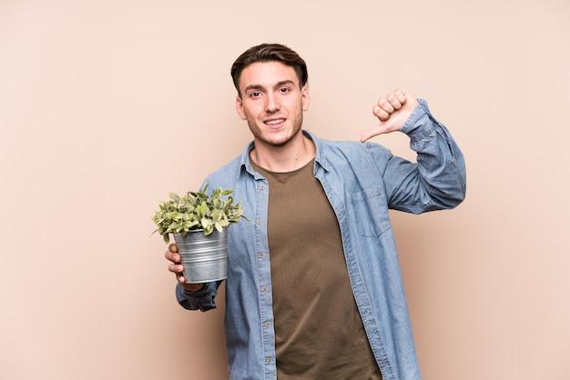 Jonge blanke man met een plant voelt zich trots en zelfverzekerd, voorbeeld te volgen.