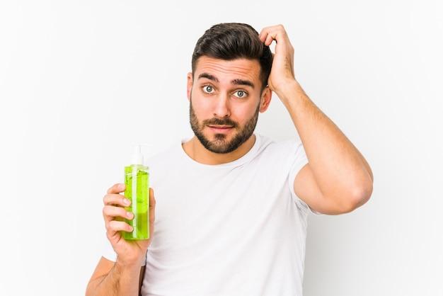 Jonge blanke man met een vochtinbrengende crème met aloë vera wordt geschokt