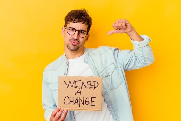 Jonge blanke man met een we hebben een bordje met verandering nodig, voelt zich trots en zelfverzekerd, voorbeeld om te volgen.