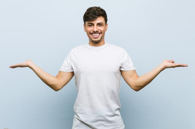 Jonge blanke man met een wit t-shirt maakt schaal met armen, voelt zich gelukkig en zelfverzekerd.