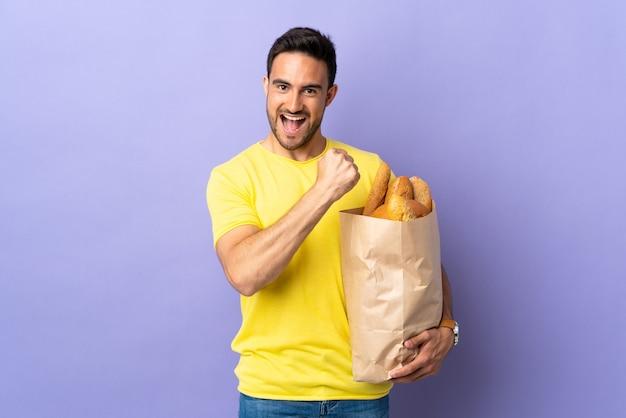 Jonge blanke man met een zak vol brood geïsoleerd op paarse achtergrond een overwinning vieren