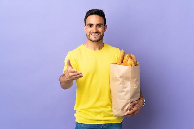 Jonge blanke man met een zak vol brood geïsoleerd op paarse achtergrond handshaking na goede deal