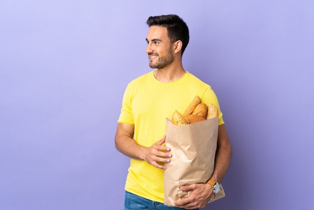 Jonge blanke man met een zak vol brood geïsoleerd op paarse achtergrond op zoek naar de zijkant
