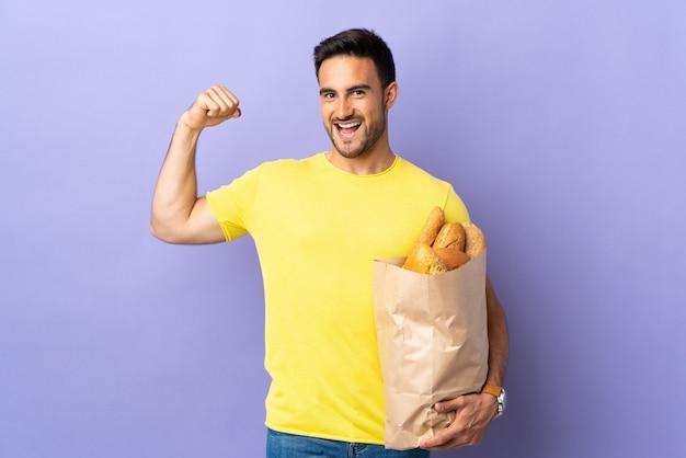 Jonge blanke man met een zak vol brood geïsoleerd op paarse achtergrond sterk gebaar maken