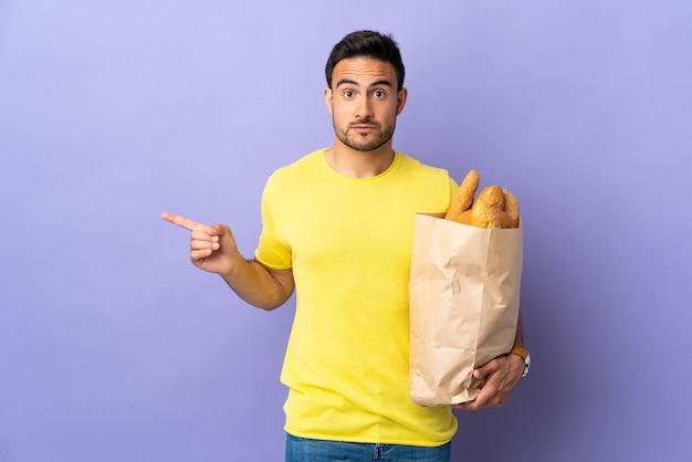 Jonge blanke man met een zak vol brood geïsoleerd op paarse achtergrond wijzend naar de zijkanten twijfels