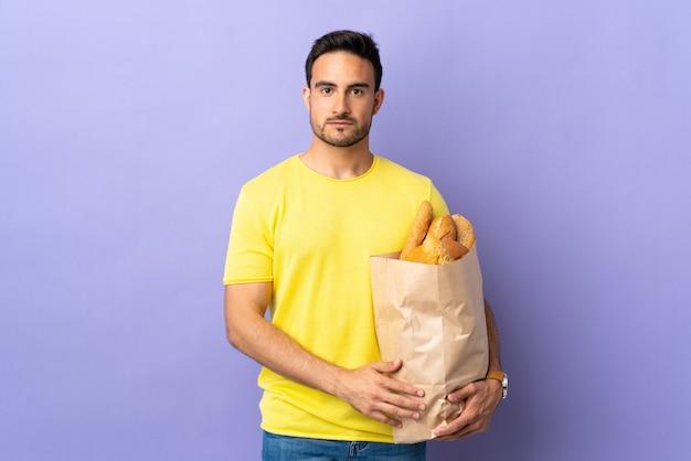 Jonge blanke man met een zak vol brood geïsoleerd op paarse muur armen gekruist