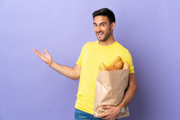 Jonge blanke man met een zak vol brood geïsoleerd op paarse muur handen naar de zijkant voor uitnodigend om te komen