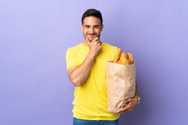 Jonge blanke man met een zak vol brood geïsoleerd op paarse muur lachen