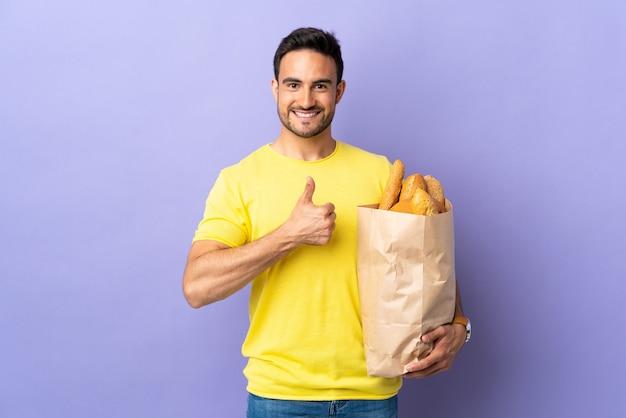 Jonge blanke man met een zak vol brood geïsoleerd op paarse muur met een duim omhoog gebaar
