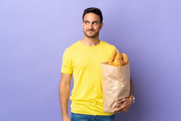 Jonge blanke man met een zak vol brood geïsoleerd op paarse muur staan en kijken naar de zijkant