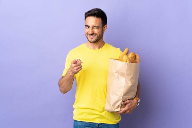 Jonge blanke man met een zak vol brood geïsoleerd op paarse muur wijst vinger naar je