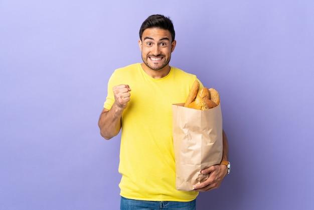 Jonge blanke man met een zak vol brood geïsoleerd vieren een overwinning