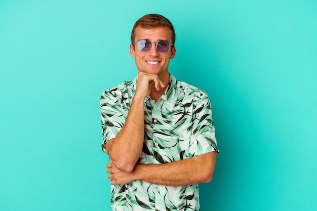 Jonge blanke man met een zomerkleren geïsoleerd op blauw glimlachend gelukkig en zelfverzekerd, kin met hand aanraken.