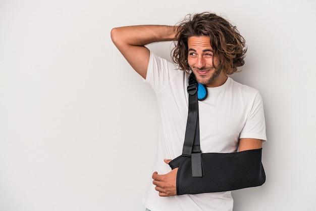 Jonge blanke man met gebroken hand geïsoleerd op een grijze achtergrond achterhoofd aanraken, denken en een keuze maken.