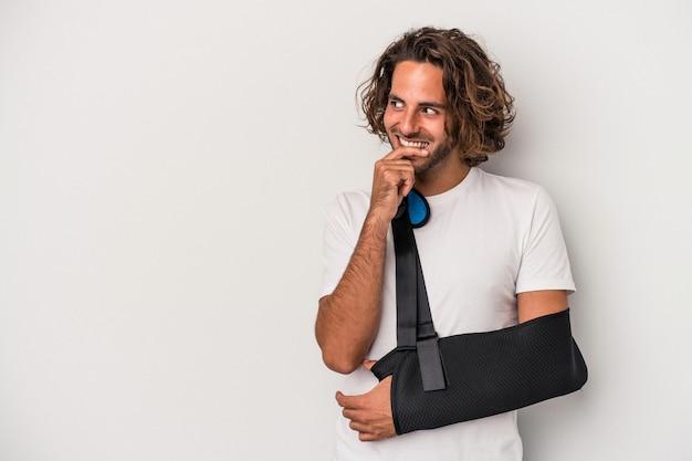 Jonge blanke man met gebroken hand geïsoleerd op een grijze achtergrond ontspannen denken over iets kijken naar een kopie ruimte.