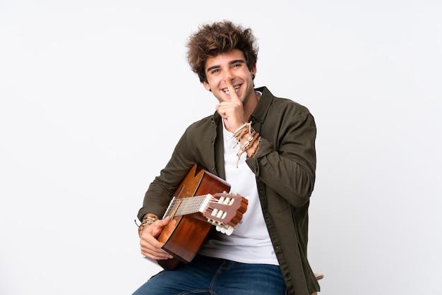 Jonge blanke man met gitaar over geïsoleerde witte muur stilte gebaar doen