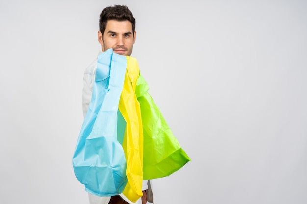 Jonge blanke man met herbruikbare boodschappentassen tegen een witte muur