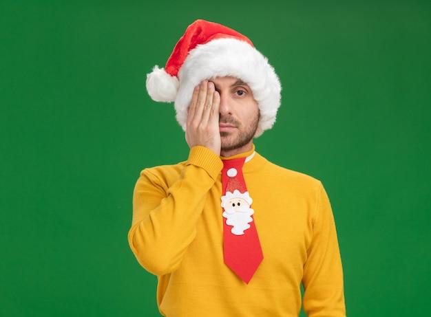 Jonge blanke man met kerstmuts en stropdas die de helft van het gezicht bedekt met hand kijken naar camera geïsoleerd op groene achtergrond met kopie ruimte