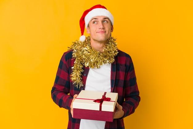 Jonge blanke man met kerstmuts met een cadeau geïsoleerd op geel, dromen van het bereiken van doelen en doeleinden