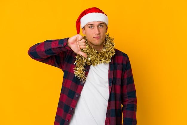 Jonge blanke man met kerstmuts met een cadeau geïsoleerd op geel met een afkeer gebaar, duimen naar beneden. meningsverschil concept.