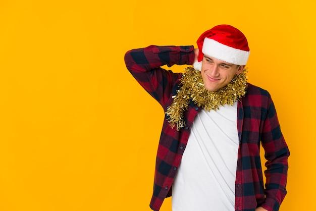 Jonge blanke man met kerstmuts met een cadeau geïsoleerd op gele muur blij, lachend en vrolijk.