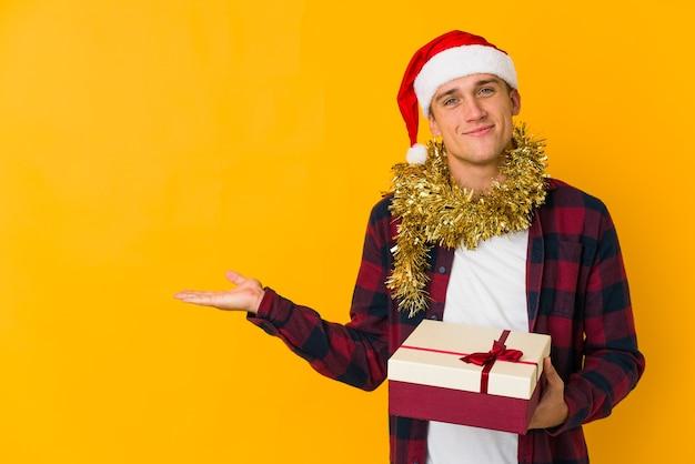 Jonge blanke man met kerstmuts met een cadeau geïsoleerd op gele muur met een kopie ruimte op een palm
