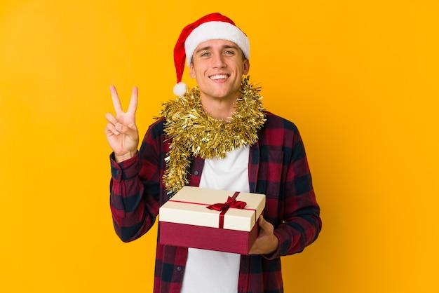 Jonge blanke man met kerstmuts met een cadeau geïsoleerd op gele muur met nummer twee met vingers.