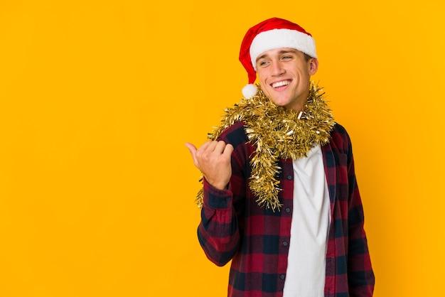 Jonge blanke man met kerstmuts met een cadeau geïsoleerd op gele punten met duimvinger weg, lachend en zorgeloos.
