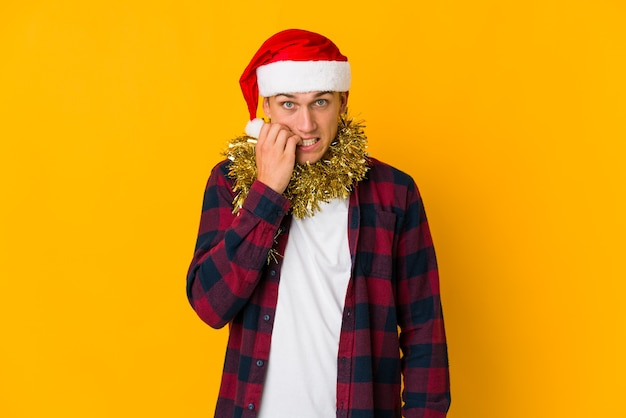 Jonge blanke man met kerstmuts met een cadeautje op geel verward, voelt zich twijfelachtig en onzeker.