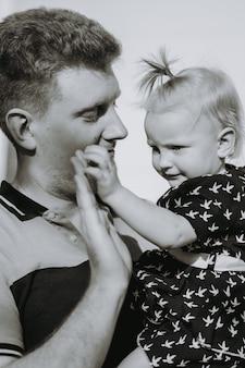 Jonge blanke man met krullend haar die teder naar zijn dochtertje kijkt